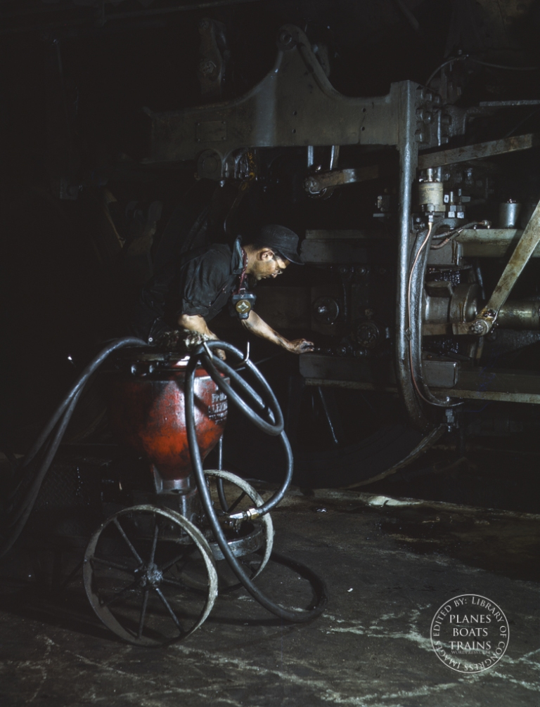 Thomas Madrigal greasing a locomotive in the roundhouse, Rock Island R.R., Blue Island, Ill